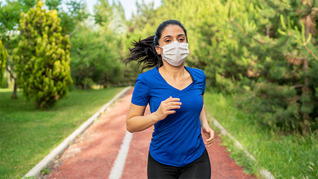 Woman with dark hair in a ponytail and a blue shirt running on a track with a mask